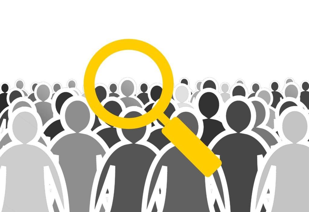 Lupe sucht nach einer Person in Menschenmenge