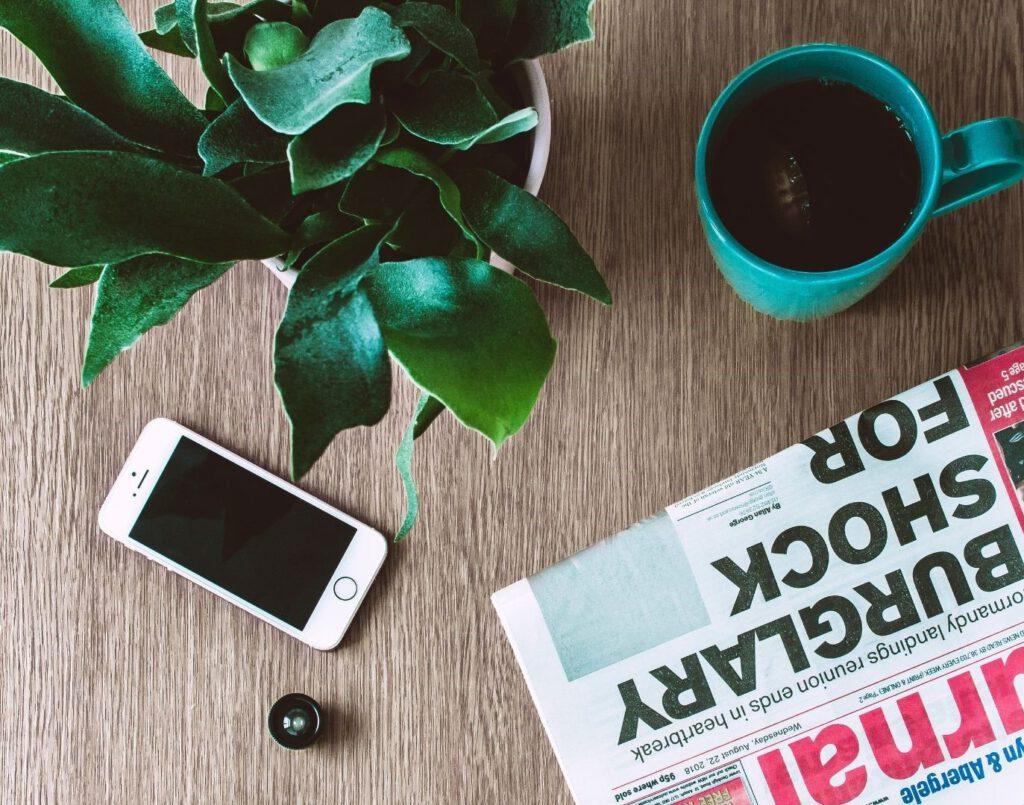 Zeitung, Handy, Pflanze und eine Tasse Kaffee auf einemTisch